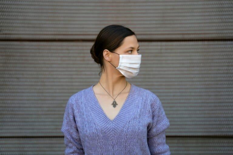 Covid-19 women in blue sweater wears white face mask