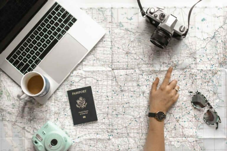 Computer sits on a map with someone pointing at a location. A camera and passport are in frame